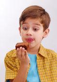 Küçük çocuk bir çikolatalı kek yeme — Stok fotoğraf