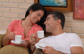 Mid adult couple drinking coffee in a living room. — Stock Photo