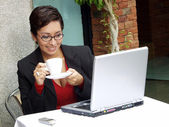 Businesswoman woman in a restaurant working on a computer. — Stock Photo