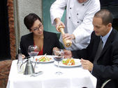 Hispanic couple at a restaurant and a waiter serving. — 图库照片