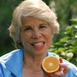 Mid adult woman drinking orange juice. Mid adult woman holding fresh oranges. - ストック写真