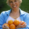 Mid adult woman holding fresh oranges. - Stock fotografie