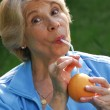Mid adult woman drinking orange juice. Mid adult woman holding fresh oranges. — Stock Photo #15620631