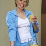Mid adult woman drinking orange juice. Woman holding orange juice jar. — Stock Photo