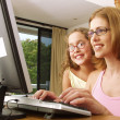 Stock Photo: Young mother and her daughter on a computer.