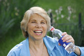 Mid adult woman holding a water bottle. — Stock Photo
