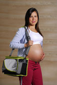 Pregnant woman holding a sport bag. — Stock Photo