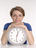 Young woman holding a clock on white background. — Stock Photo
