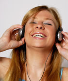 Ung kvinna lyssnar musik med hörlurar. — Stockfoto