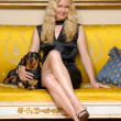 Young blonde woman with a little dog sitting on an elegant yellow sofa. — Stock Photo #15771531