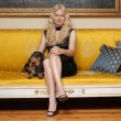 Young blonde woman with a little dog sitting on an elegant yellow sofa. — Stock Photo #15771533
