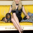 Young blonde woman with a little dog sitting on an elegant yellow sofa. — Stock Photo #15771549