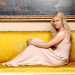 Beautiful blonde woman sitting on a yellow sofa. — Stock Photo