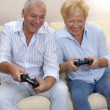 Senior couple playing video games holding joysticks. — Stock Photo