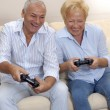 Senior couple playing video games holding joysticks. - Stock Photo