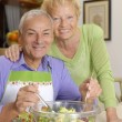 Happy senior couple preparing vegetable salad in the kitchen. - Stock Photo