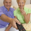 Happy senior couple watching television together.Senior couple changing tv channels. — Stock Photo