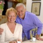 Happy senior couple drinking coffee at kitchen. — Stock Photo #15771747