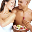 Young hispanic couple enjoying and eating vegetable salad on white background. - Stock Photo