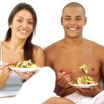 Young hispanic couple enjoying and eating vegetable salad on white background. — Stock Photo #15772175