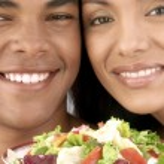 Young hispanic couple enjoying and eating vegetable salad on white background. — Stock Photo #15772179