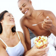 Young hispanic couple enjoying and eating fruit salad on bed. — Stock Photo