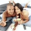 Young hispanic couple enjoying and eating fruit salad on bed. — Stock Photo #15772419