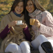 Outdoors autumn young women enjoying and drinking hot coffe. - Foto de Stock