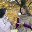 Outdoors autumn young women enjoying and drinking hot coffe. — Stock Photo