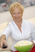 Mature woman enjoying in a living room eating popcorn. — Stock Photo