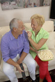 Happy senior couple enjoying watching television together and eating popcorn. — Stock Photo