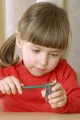 Little girl sharpening a pencil. — Stock Photo