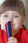 Little girl portrait drawing and playing with a crayon. — Stock Photo