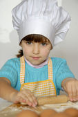 Little girl cooking a pizza in a kitchen.Little kid in a kitchen. — Stock Photo