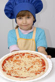 Little girl holding a pizza.Little girl with a chef cap holding a pizza. — Stock Photo