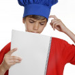 Foto Stock: Little kid chef holding a note book on white background.