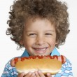 Little kid eating hot dog,Kid holding hot dog. - Stock Photo