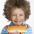 Little kid eating hot dog,Kid holding hot dog. - Foto Stock
