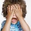 Stock Photo: Expressive surprised kid covering his eyes.