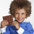 Little kid eating chocolate,holding chocolate bar. — Stock Photo #16240473