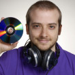 Young disk jockey holding a compact disc.Young man using headphones. - Стоковая фотография