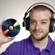 Young disk jockey holding a compact disc.Young man using headphones. — Stock Photo