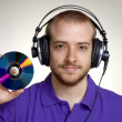 Young disk jockey holding a compact disc.Young man using headphones. - 