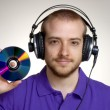 Young disk jockey holding a compact disc.Young man using headphones. - Stock Photo