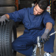 A young man working in the garage - Stock Photo