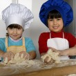 Two Little girls cooking a pizza in a kitchen.Little kid in a kitchen together. — Stock Photo #16240663