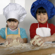 Two Little girls cooking a pizza in a kitchen.Little kid in a kitchen together. — Foto Stock