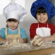 Two Little girls cooking a pizza in a kitchen.Little kid in a kitchen together. — 图库照片
