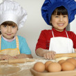 Two Little girls cooking a pizza in a kitchen.Little kid in a kitchen together. — Foto de Stock