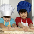Two Little girls cooking a pizza in a kitchen.Little kid in a kitchen together. — Stock Photo #16240691